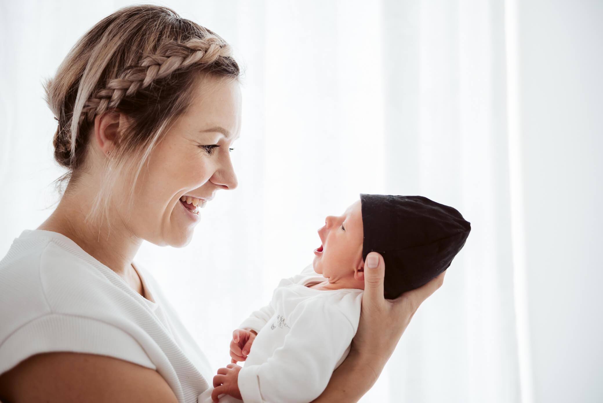 Mama kijkt baby liefdevol in de ogen tijdens newbornshoot