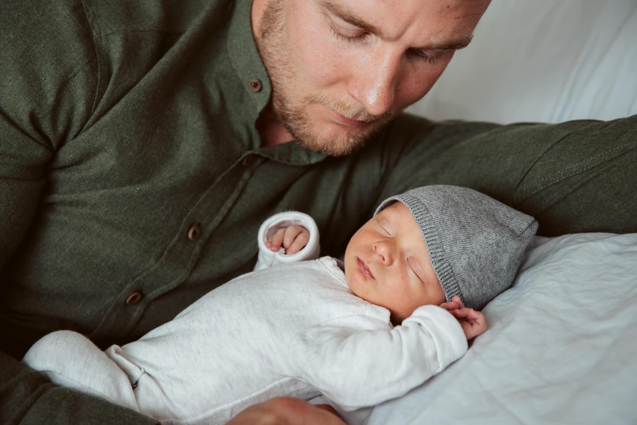 Papa kijkt liefdevol naar baby tijdens newbornshoot