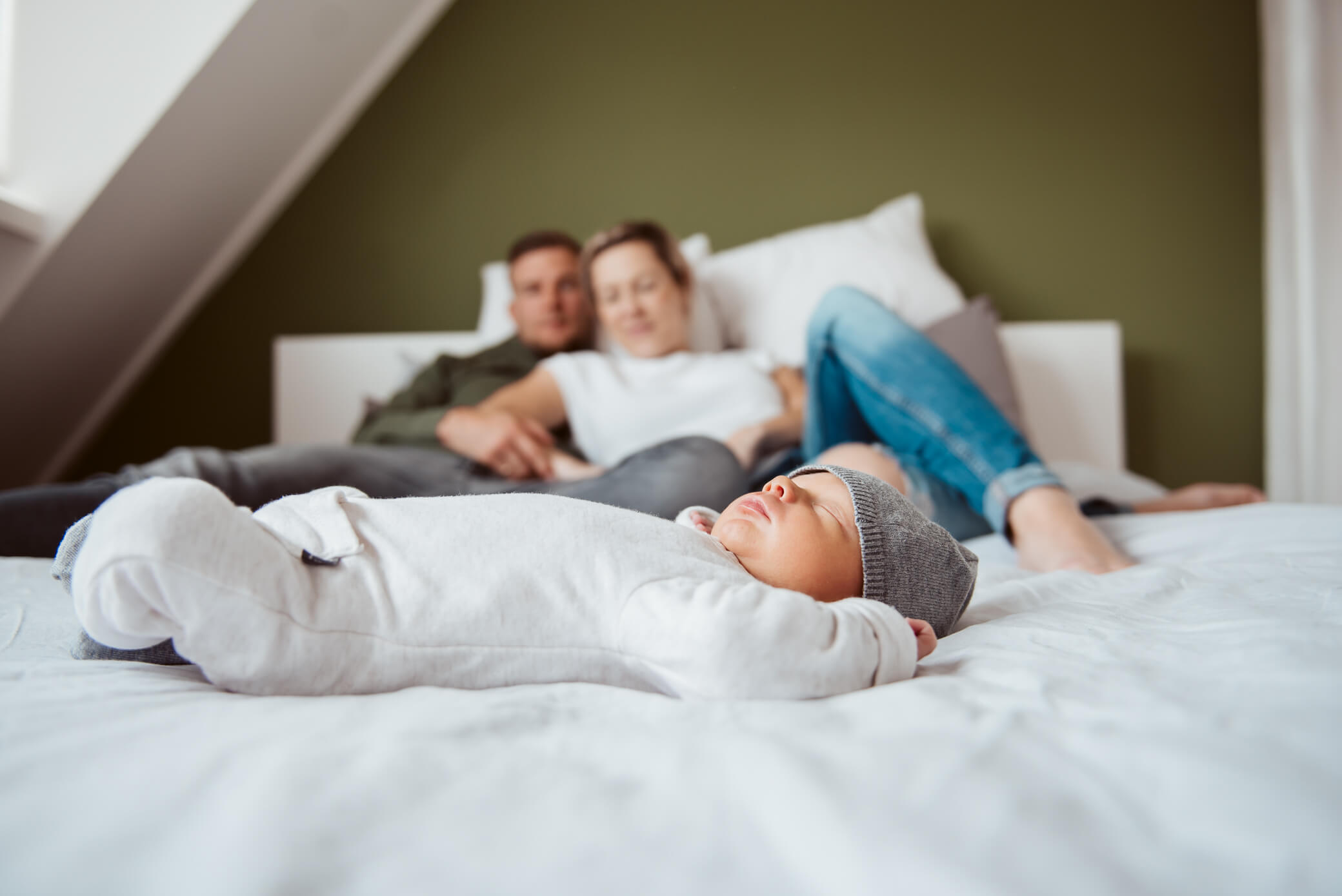 Baby op grote bed met ouders op de achtergrond tijdens newbornshoot