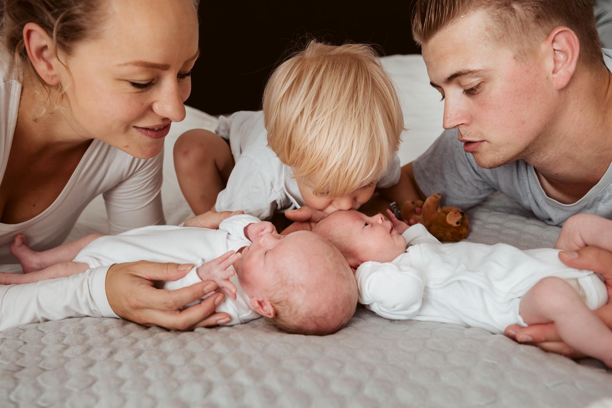 Grote broer geeft kusje en trotse ouders kijken toe
