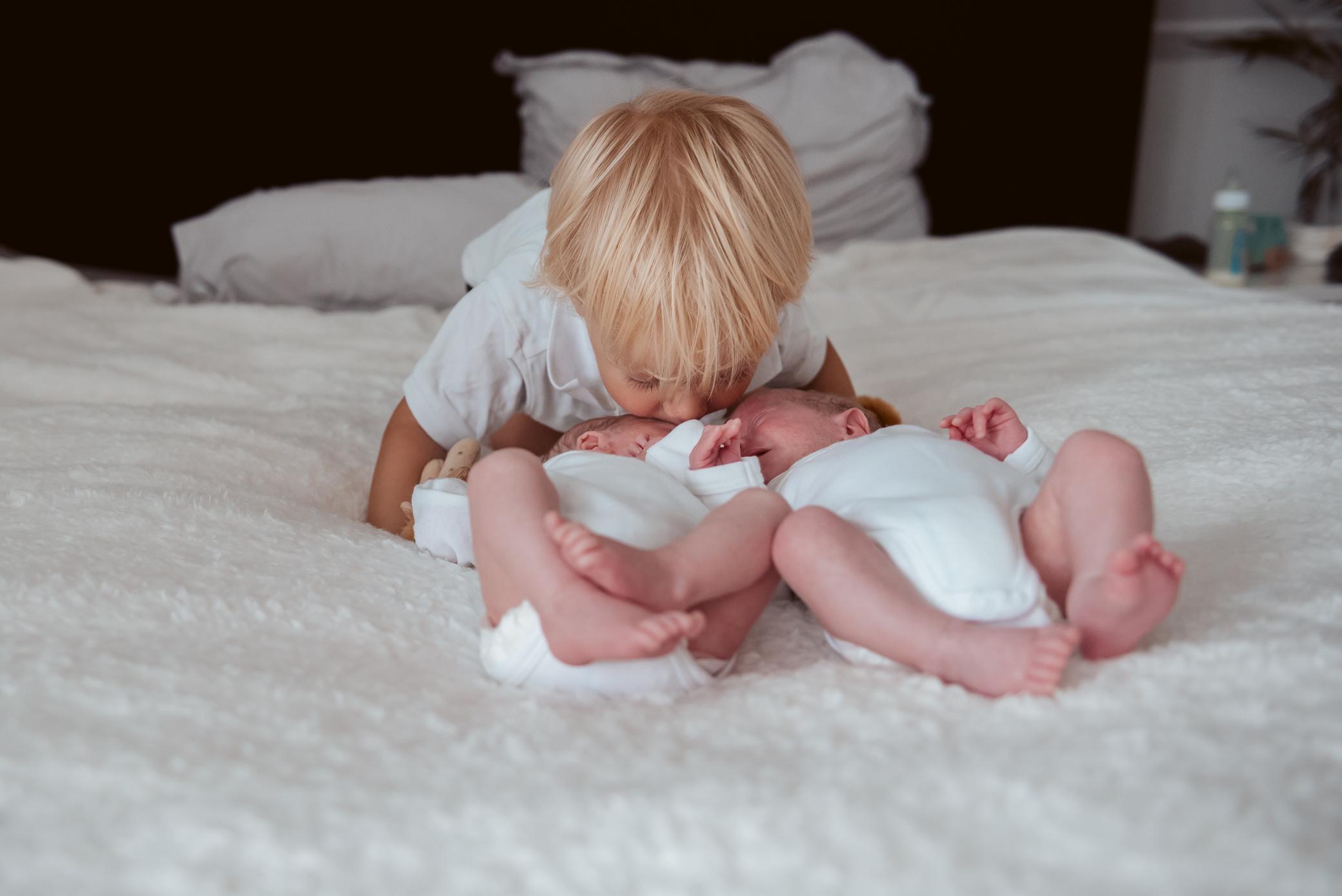 Grote broer geeft kusje aan zijn tweelingbroertjes