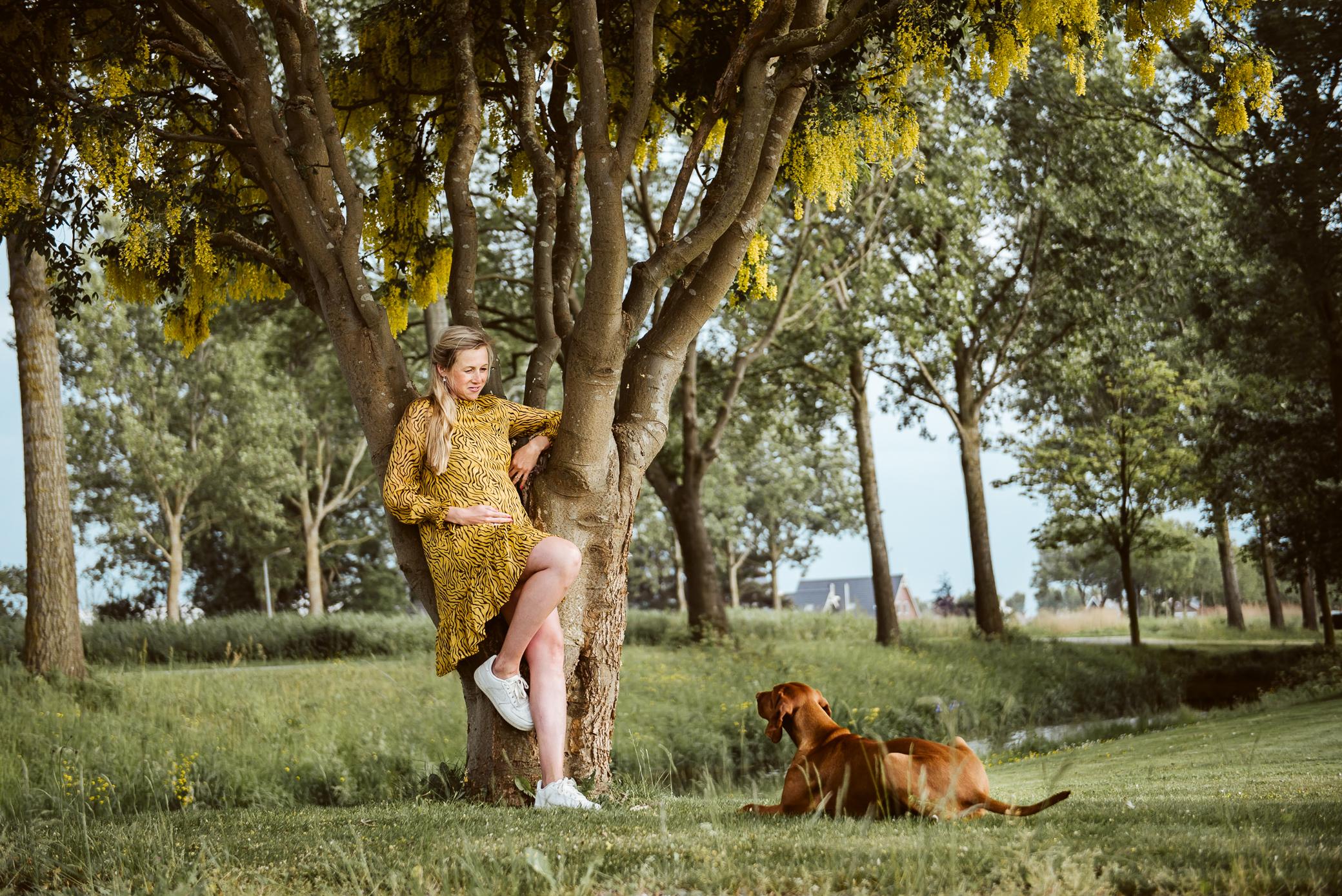Zwangere mama kijkt naar hond onder de gouden regen